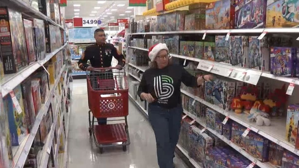 U.S. Marines and Big Brothers/Big Sisters staff members shopping for holiday party gifts (WBAY photo)
