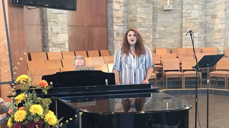 """Eva Thelen-Dunphy sings the """"Ave Maria"""" while her family accompanies her on the piano."""