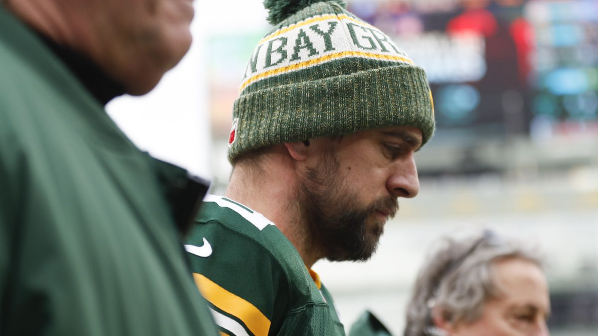 CORRECTS TO REMOVE SCORE- Green Bay Packers' Aaron Rodgers is taken to the locker room to be...