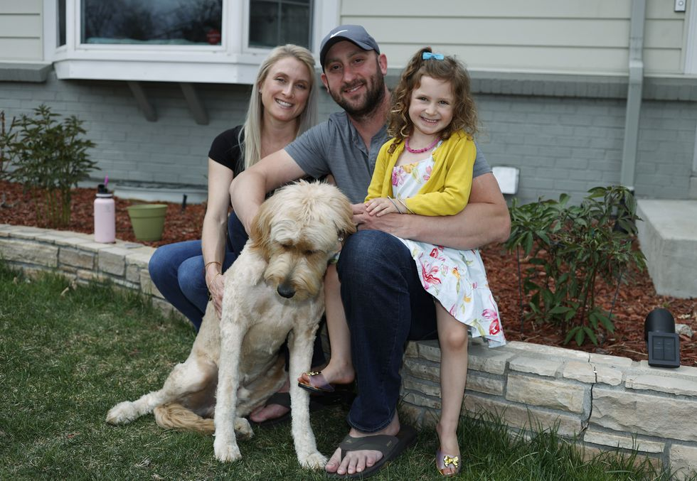 Eli Oderberg, center, sits with Katie Evers, left, their 4-year-old daughter, Everlee, and the couple's goldendoodle outside their home in southeast Denver on Thursday, April 30, 2020. Oderberg, like 30 million people around the United States who have filed for unemployment benefits after losing their jobs during the coronavirus pandemic, is facing the specter of paying the monthly rent with the flip of the calendar.