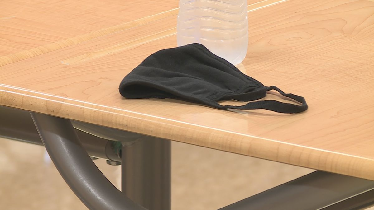 Mask sits on desk in a classroom