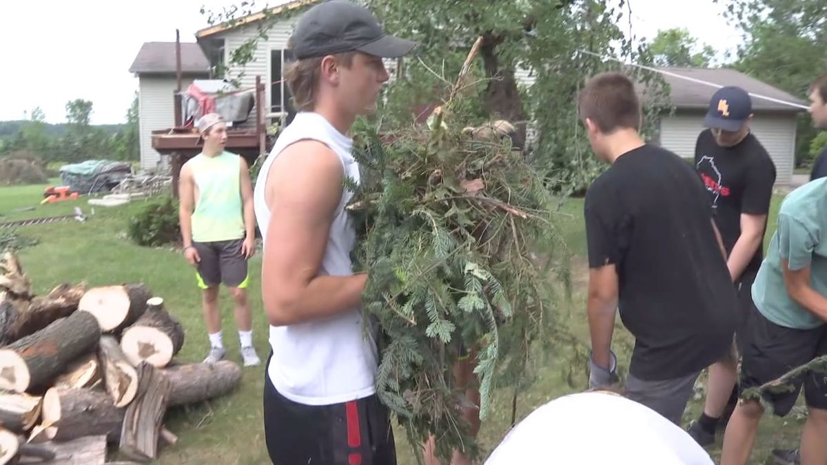 Players on the New London high school football team help clean up storm damage on neighbors'...