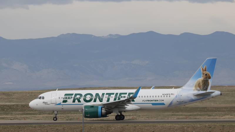 A Frontier Airlines jetliner taxis to a runway for take off from Denver International Airport...