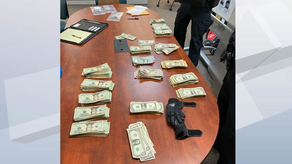 Green Bay police count money taken from the Chase Bank robbery suspect on January 7, 2021