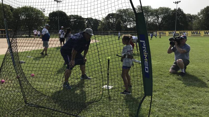 A Kids Camp camper works on her softball swing.