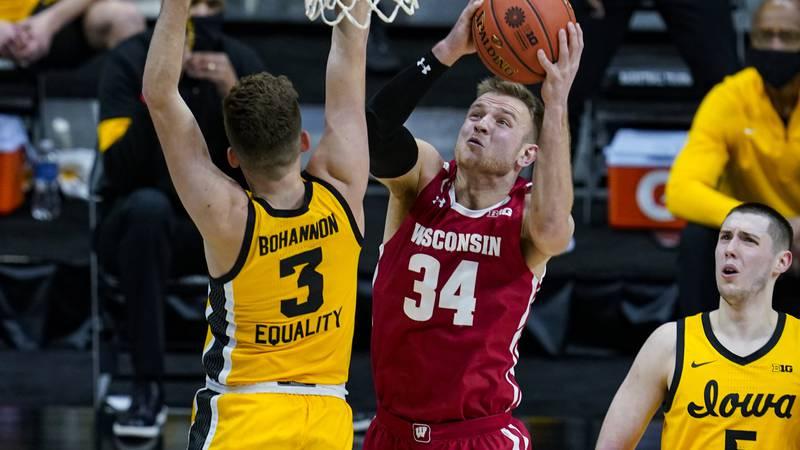 Wisconsin guard Brad Davison (34) shoots over Iowa guard Jordan Bohannon (3) during the first...