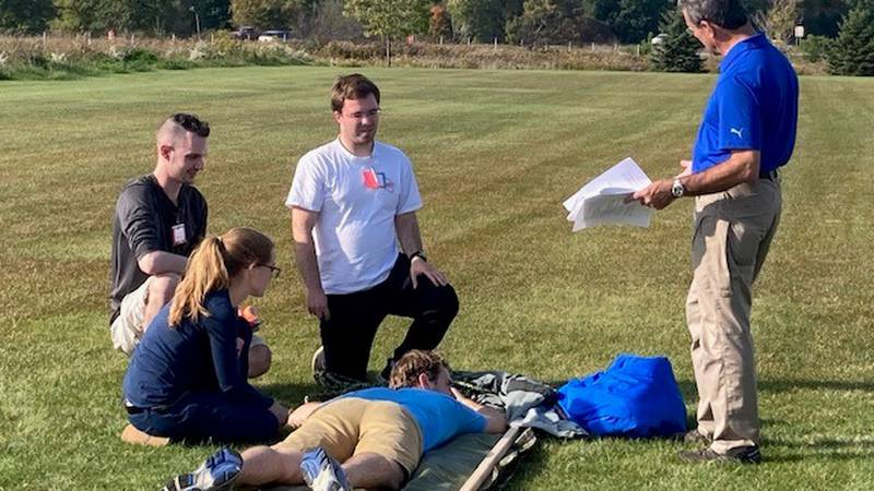 Dr. Michael Medich (standing) helps teach medical school students how to think on their feet,...
