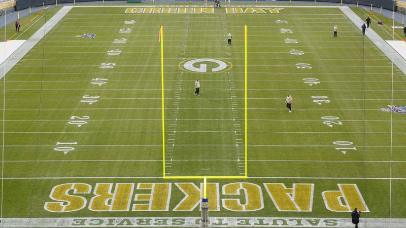 Workers prepare Lambeau Field before an NFL football game between the Green Bay Packers and...