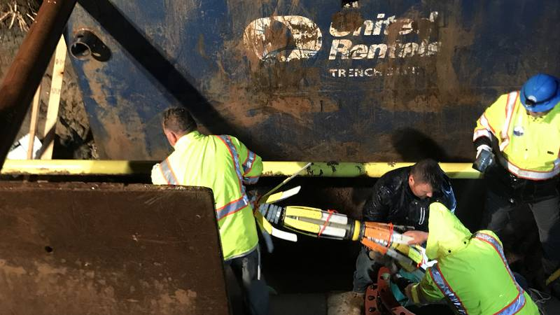 Water utility crews safely pull a robot, that had been stuck inside one of the city's main...
