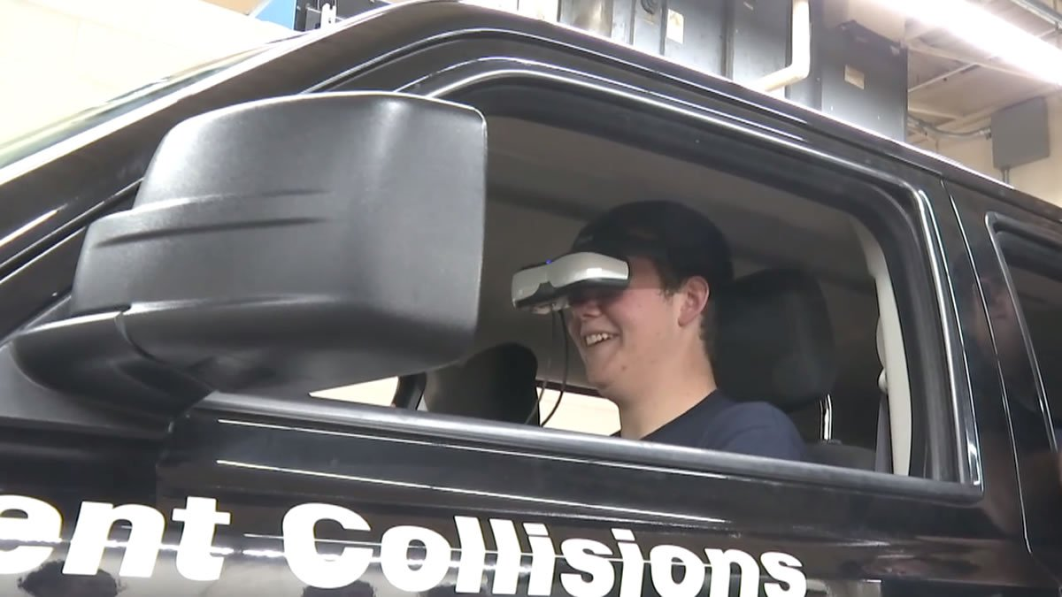 """A student wearing a virtual reality headset takes the wheel in the """"Arrive..."""