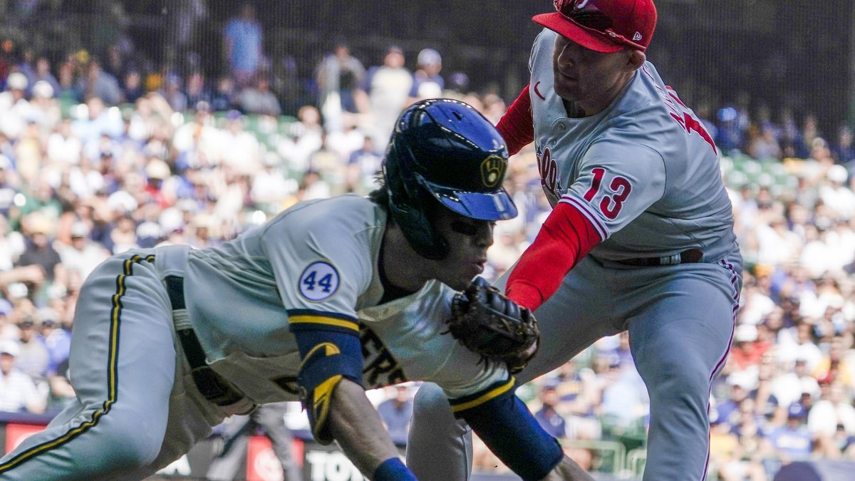 Philadelphia Phillies' Brad Miller tags out Milwaukee Brewers' Christian Yelich at first during...