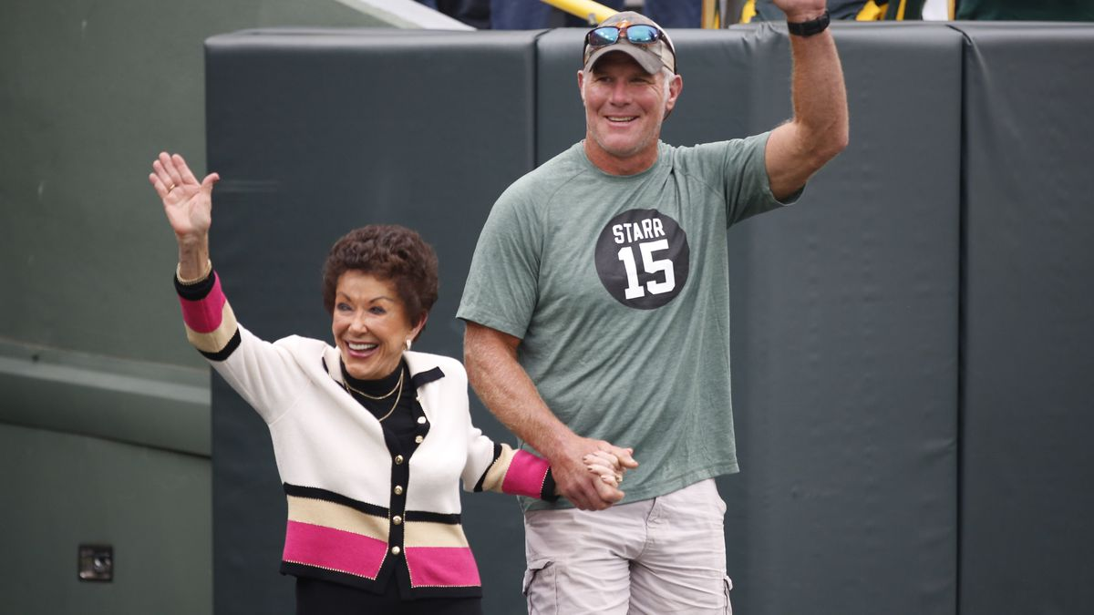 Former Green Bay Packers quarterback Brett Favre escorts Cherry Louise Morton, wife of former Green Bay Packers Bart Starr out of the tunnel before an NFL football game between the Green Bay Packers and the Minnesota Vikings Sunday, Sept. 15, 2019, in Green Bay, Wis. (AP Photo/Matt Ludtke)