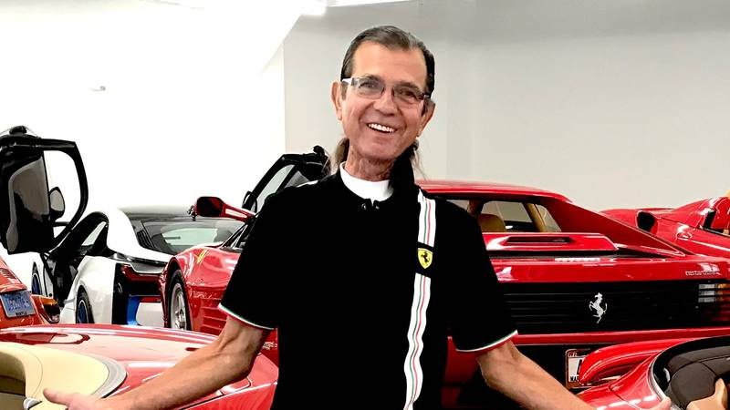 Dale Besson poses with some of his exotic cars on display at The Automobile Gallery in Green Bay.