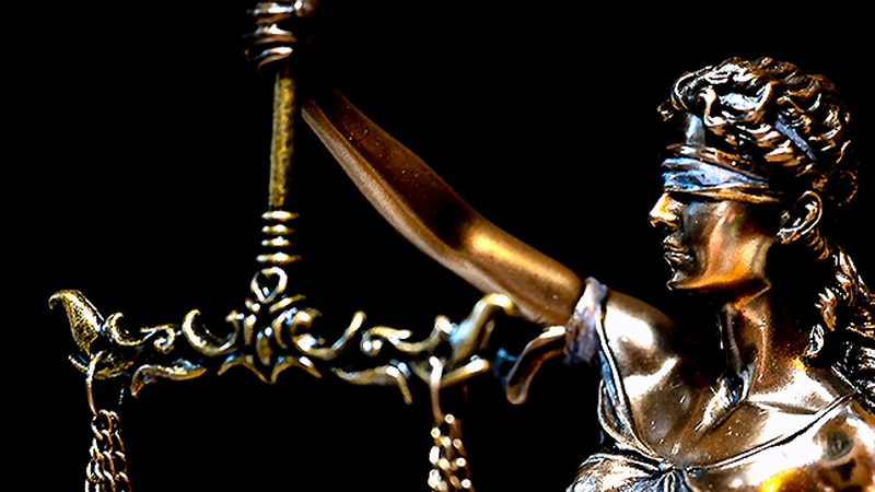 Lady Justice holds the scales of justice, symbolizing fairness in the judicial process.