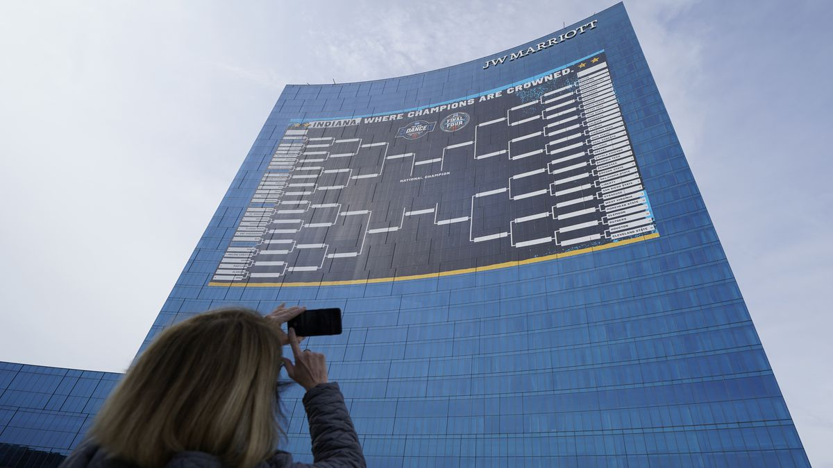 Lisa Moeller takes a photo of the NCAA bracket for the NCAA college basketball tournament on...