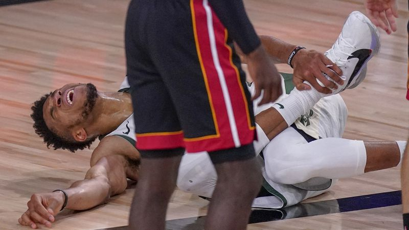 Milwaukee Bucks' Giannis Antetokounmpo reacts after hurting his ankle during the first half of...