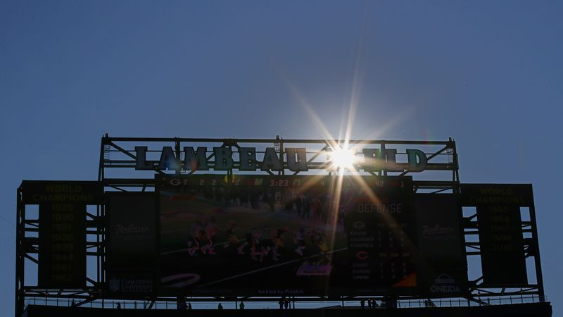 The sun peaks through the scoreboard at Lambeau Field during an NFL football game between the...