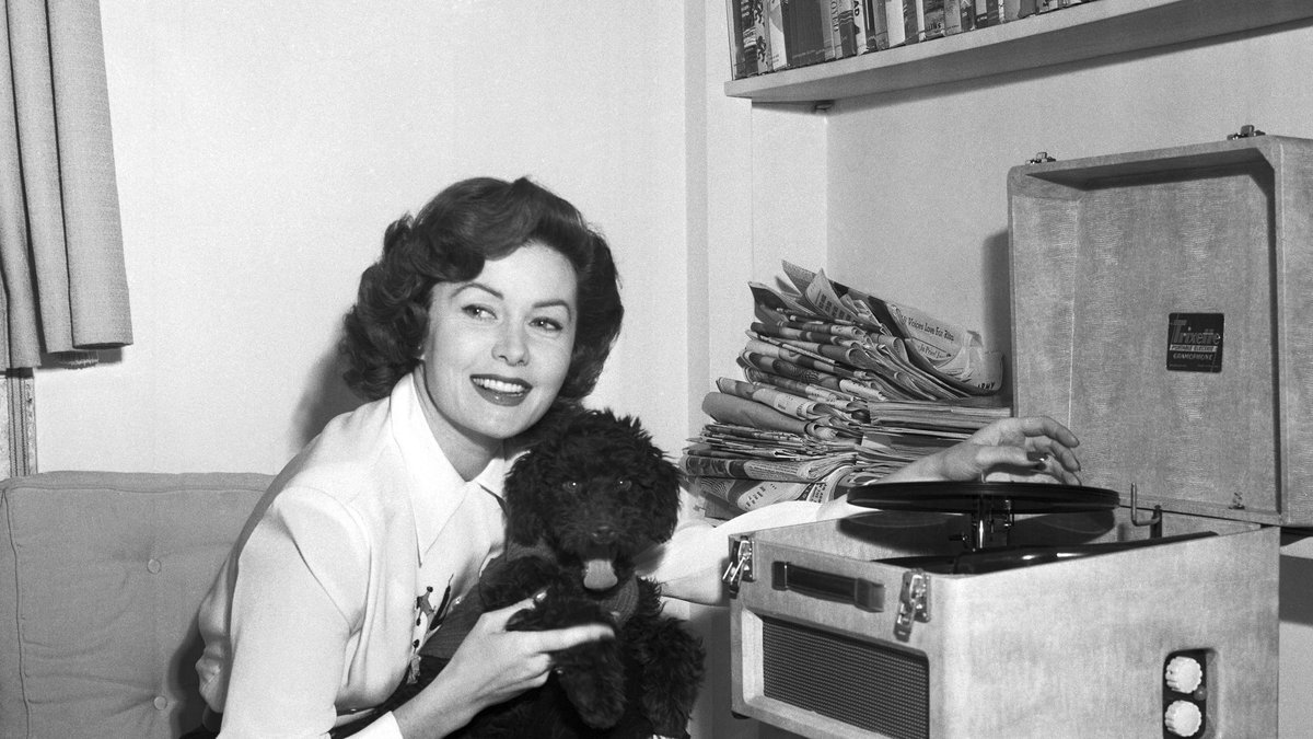 In this March 1, 1955 file photo, Actress Rhonda Fleming reads in her penthouse apartment in...