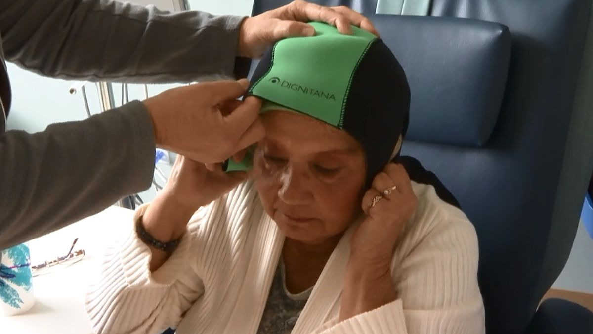 A patient puts on the Dignicap, which helps cancer patients avoid hair loss during chemotherapy...
