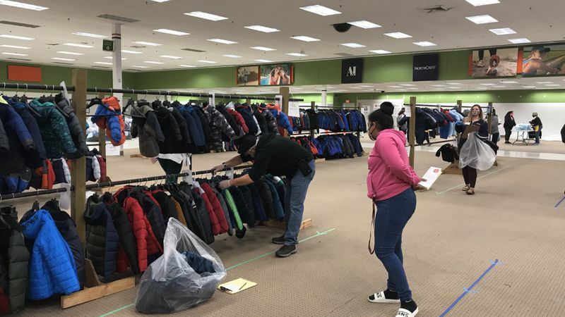 A volunteer helps a mother pick out coats for her kids during The Salvation Army's annual Coats...