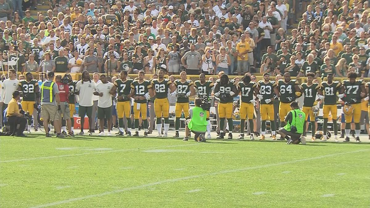Green Bay Packers stand on the sidelines of a game in 2017 with their arms linked in solidarity with NFL players who were taking a knee during the national anthem to protest police brutality and racial injustice (WSAW file photo)