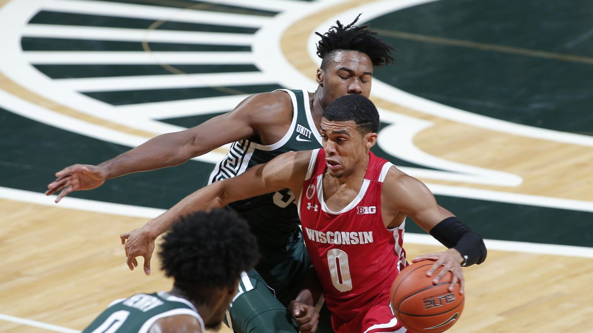Wisconsin's D'Mitrik Trice, right, drives against Michigan State's Julius Marble II during the...