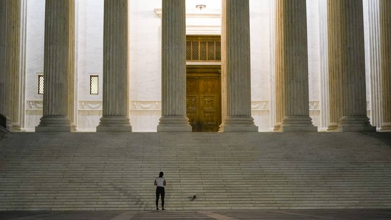 People lay flowers and light candies outside the Supreme Court Friday, Sept. 18, 2020, in...