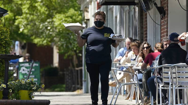 FILE - A member of the wait staff delivers food to outdoor diners along the sidewalk at the...