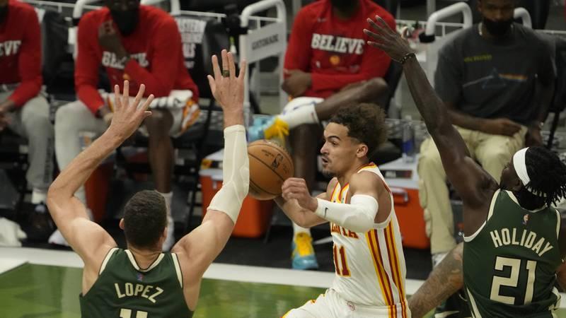 Atlanta Hawks' Trae Young drives between Milwaukee Bucks' Jrue Holiday and Brook Lopez during...