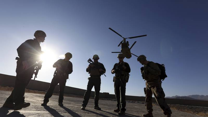 FILE - In this Nov. 30, 2017, file photo, American soldiers wait on the tarmac in Logar...