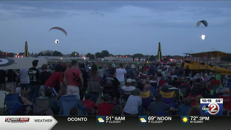 Parachutists with flares sail past the flight line during EAA AirVenture's night time air show