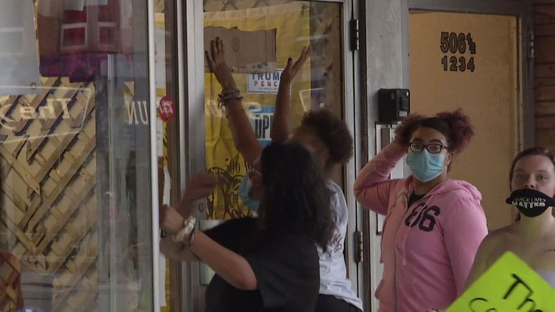 Protesters pound on the window of Outagamie County Republican Party offices in downtown Appleton