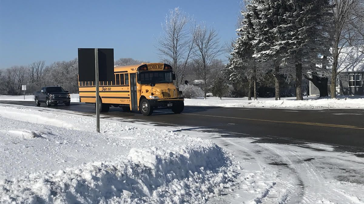 A school bus drives away during the crash investigation on Highway 73. Officials tell us a car passing the school bus hit two children, killing one (WBAY photo)
