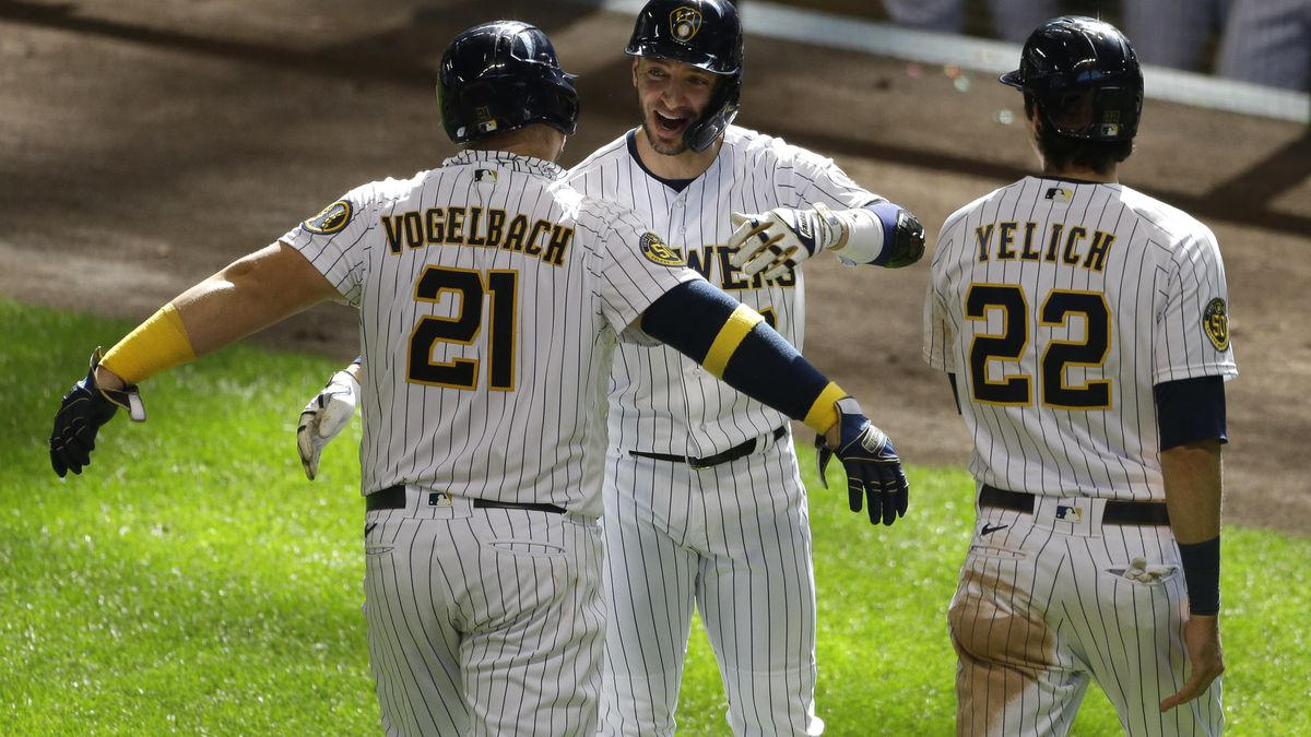 Milwaukee Brewers' Daniel Vogelbach, left, is congratulated by Ryan Braun, center,  and Christian Yelich, right, after hitting a three-run home run during the sixth inning of a baseball game against the Kansas City Royals Sunday, Sept. 20, 2020, in Milwaukee. (AP Photo/Aaron Gash)