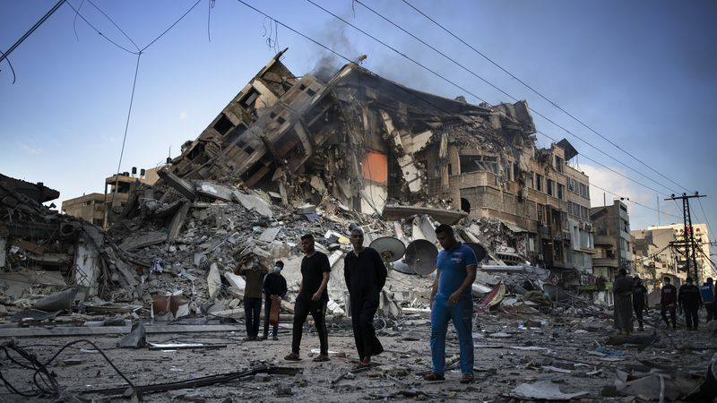 Palestinians walk next to the remains of a destroyed 15 story building after being hit by...